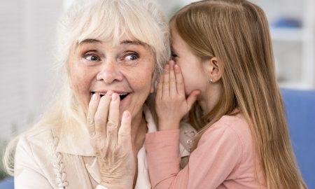 little-girl-telling-secret-to-grandma